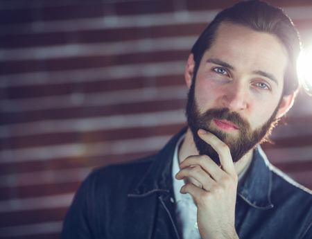 hand on the chin: Portrait of confident man with hand on chin against wall Stock Photo