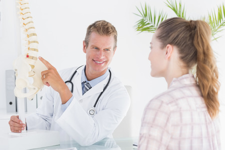 orthopaedic: Doctor explaining anatomical spine to his patient in medical office