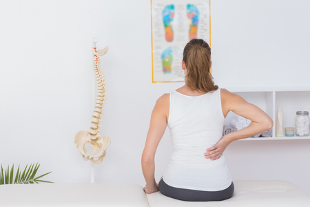 woman pain: Wear view of patient with back pain in medical office Stock Photo