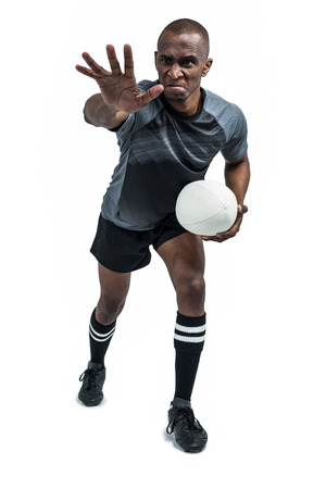 gesturing: Aggressive rugby player gesturing while holding ball over white background