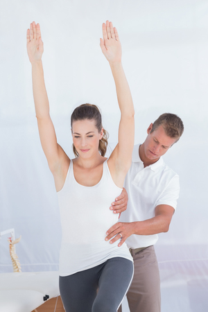 coccyx bone: Doctor examining his patient back in medical office Stock Photo