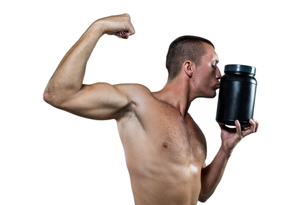 nutritional supplement: Shirtless athlete flexing muscles while kissing nutritional supplement container against white baackground