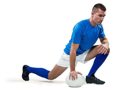 ball stretching: Full length of rugby player stretching with ball against white background