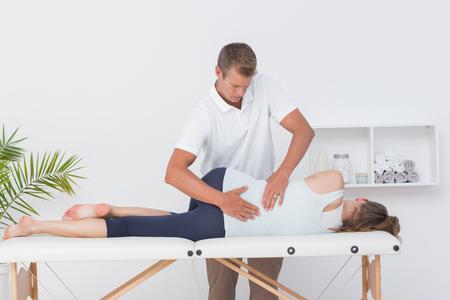 dolor  muscular: Doctor que examina a la mujer de vuelta en el consultorio m�dico