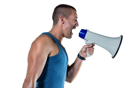 yelling: Angry male trainer yelling through megaphone against white background Stock Photo