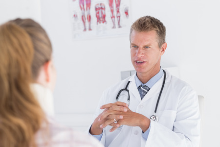 neck brace: Doctor talking to patient wearing neck brace in medical office Stock Photo