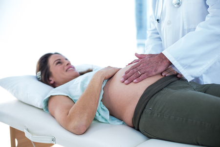 gynaecologist: Cropped image of doctor examining smiling pregnant woman in clinic