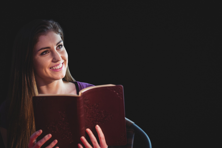 methodist: Woman praying with her bible on black background