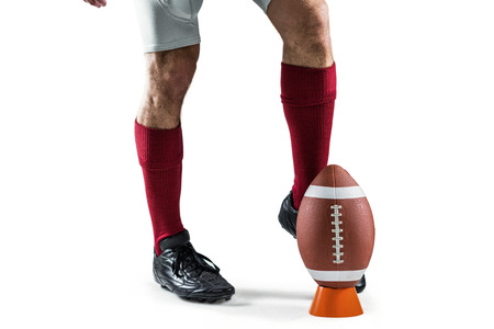kicking: Low section of sportsman kicking ball against white background Stock Photo