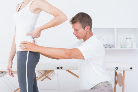 muscle retraining: Doctor examining his patient back in medical office Stock Photo
