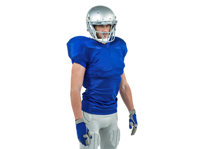 cut the competition: Confident American football player standing against white background