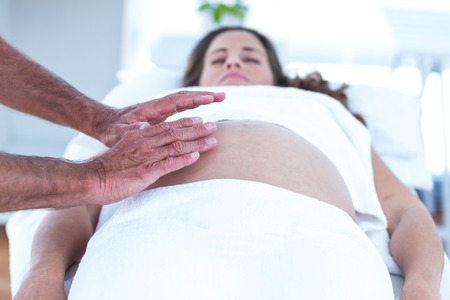 masseur: Cropped image of masseur massaging pregnant woman lying on bed in spa