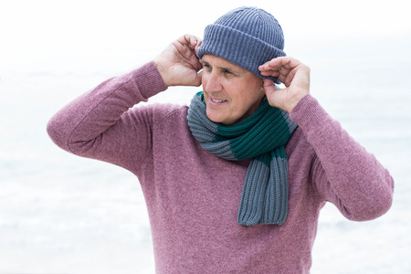 short wave: Smiling man wearing warm clothes at the beach