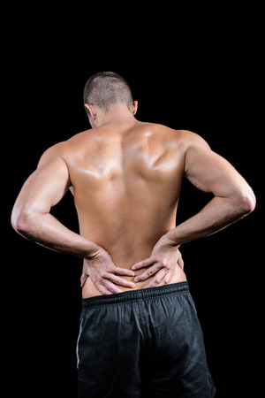 back sprains: Rear view of shirtless man touching back against black background