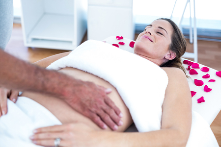 masseur: Pregnant woman receiving massage from masseur in spa