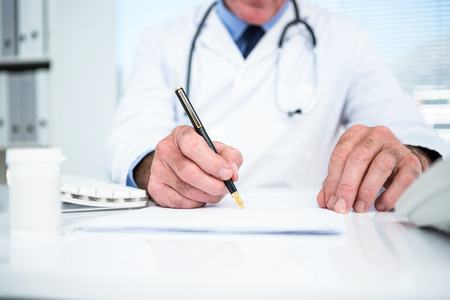 stethoscope: Midsection of doctor writing on paper at clinic