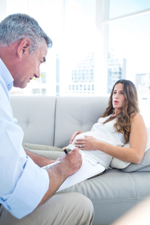 psychiatrist: Preganant woman talking with psychiatrist while relaxing at home