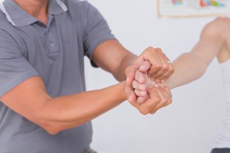 fisioterapia: M�dico estirar un brazo de mujer joven en el consultorio m�dico