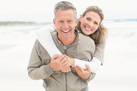 sonriente: Sonriente pareja sosteniendo entre sí en la playa