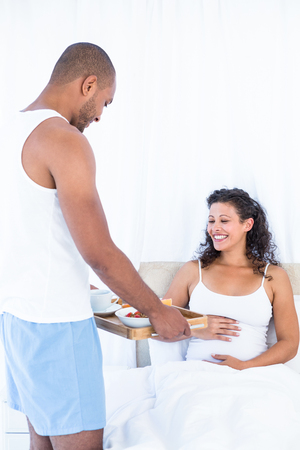 breakfast in bed: Husband with breakfast tray for happy pregnant wife on bed at home