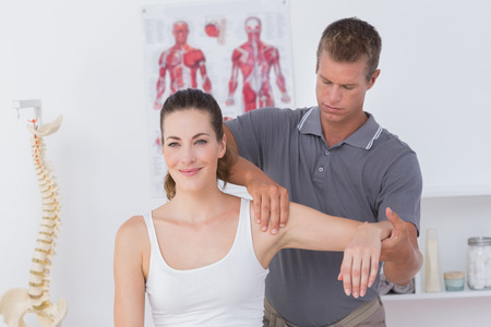 Doctor stretching a young woman arm in medical office Stock Photo