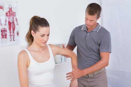 fisioterapia: Doctor que examina el brazo del paciente en el consultorio m�dico