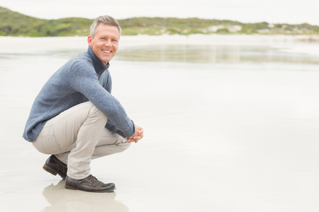 crouched: Man crouched down at the shore of the beach