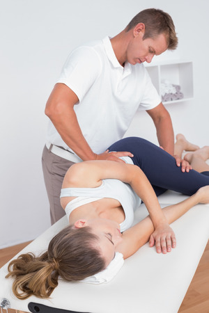 fisioterapia: Doctor stretching a young woman back in medical office Foto de archivo