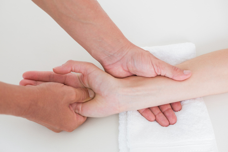 physiotherapist: Physiotherapist doing hand massage in medical office