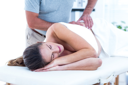 masseur: Midsection of masseur giving massage to woman in spa