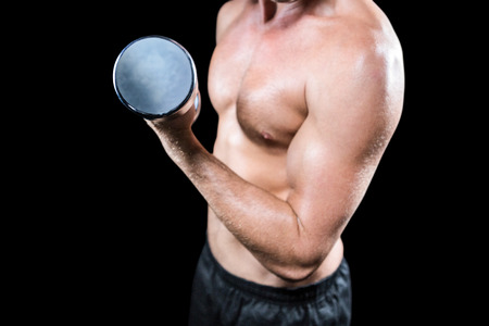 free weight: Midsection of shirtless sports player working out with dumbbell against black background
