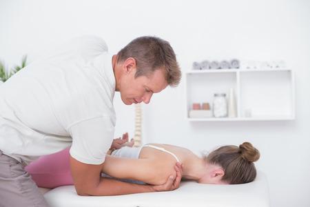 fisioterapia: Fisioterapeuta haciendo masaje en el cuello a su paciente en el consultorio m�dico Foto de archivo