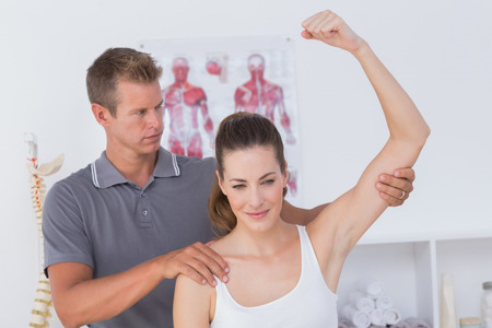 physiotherapy: Doctor stretching a young woman arm in medical office Stock Photo
