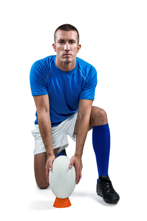 player: Full length portrait of rugby player placing ball against white background