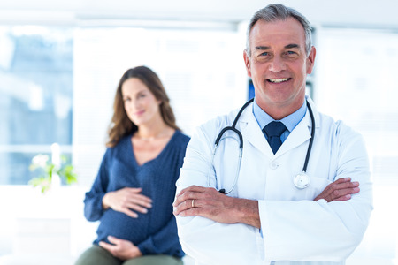 mid adult male: Portrait of smiling male doctor with pregnant woman in background at clinic