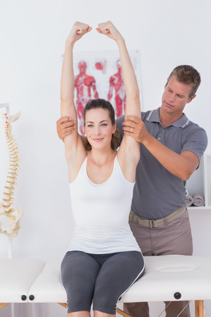 hand therapy: Doctor stretching a young woman arm in medical office Stock Photo