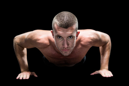 push ups: Portrait of confident shirtless athlete doing push ups against black background