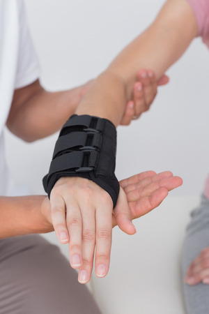 physiotherapy: Doctor examining a woman wrist in medical office