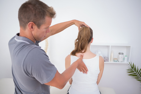 neuromuscular reeducation: Doctor examining his patient back in medical office Stock Photo