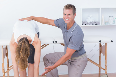 spinal adjustment: Happy doctor stretching a woman back in medical office
