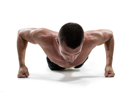 push ups: Fit shirtless athlete doing push ups against white background