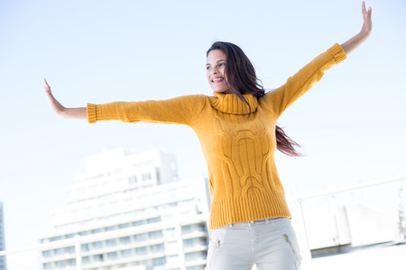 arms out: Happy woman standing with arms out outside Stock Photo