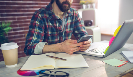 Midsection of editor using smartphone while working in office