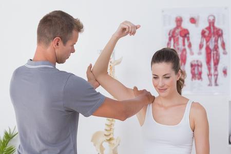 의료 사무실에서 젊은 여자의 팔을 스트레칭 의사
