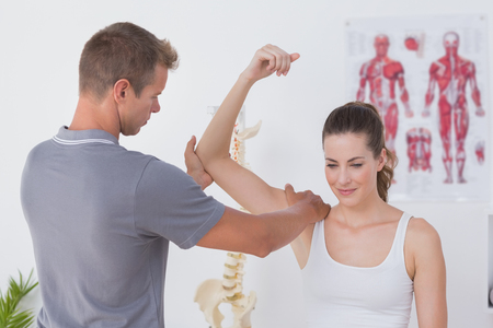 Doctor stretching a young woman arm in medical office Stockfoto