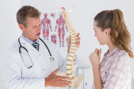 columna vertebral: M�dico explicando columna vertebral anat�mica a su paciente en el consultorio m�dico Foto de archivo