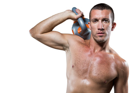 lean out: Portrait of confident shirtless male crossfitter holding kettlebell against white background