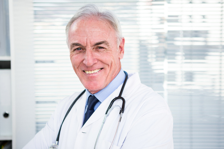 gynaecologist: Portrait of happy doctor with stethoscope around his neck at clinic Stock Photo