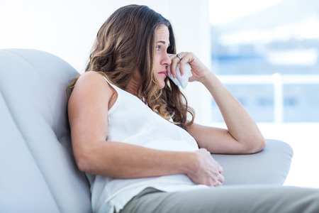 Sad pregnant woman sitting on sofa at home Stock Photo