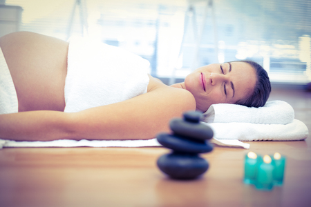 massage therapist: Pregnant woman relaxing with eyes closed in spa Stock Photo